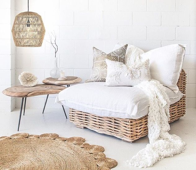 corner room, white floor, wooden side table, rattan lounge chair with white cushions, rattan rug, rattan pendant