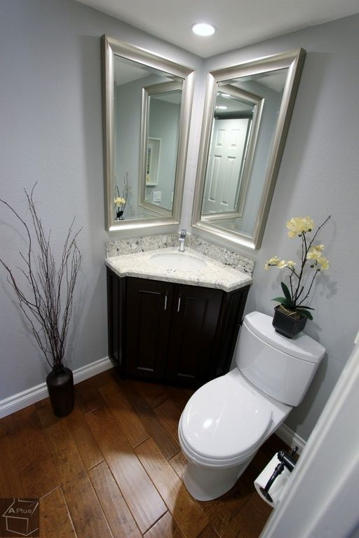 corner vanity with marble top, dark wooden cabinet on triangular shape, tall mirror on two sides of the wall