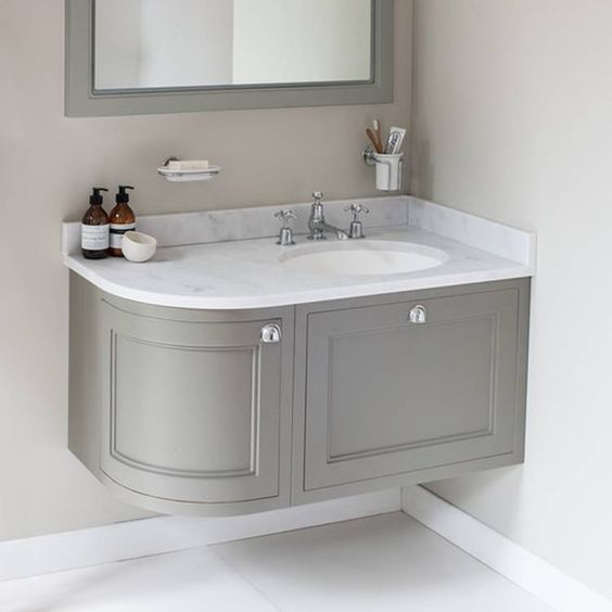 corner vanity with white marmer top, white sink, grey cabinet, all floating, grey framed mirror, silver faucet