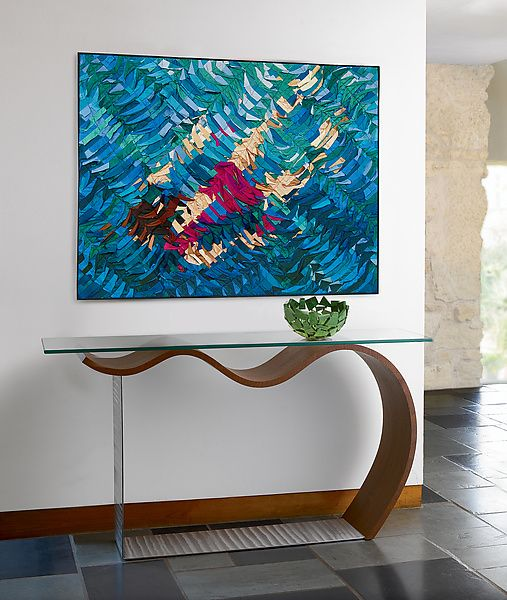 cosole table with clear top, wooden wave under, clear support, vase, abstract picture