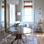 Dining Area With Wooden Floor, Beige Wall, Windows, White Chair On The Corner, Wooden Round Dining Table, Acrylic Chairs, Chandelier
