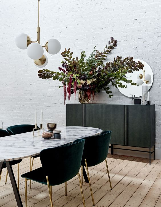 dining area, wooden floor, marble curvy table, green velvet chairs, golden legs, white textured wall, black cabinet, mirror, white pendant