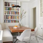 Dining Corner Nook With Wooden Table, Wooden Bench With White Cushion, White Chairs, White Built In Bookshelves, Pendant