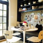 Dining Nook With Black Bench, Black Cushion, White Table, White Chairs, Black Shelves On Top Of The Bench, Board