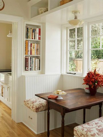 dining nook with white bench with flowery cushions, white built in shelvs for books, shelves on top, windows, lamp, wooden table