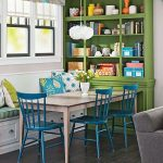 Dining Nook With White Bench With Green Cushion, Pink Table, Blue Chairs, Green Wooden Shelves, Curtain
