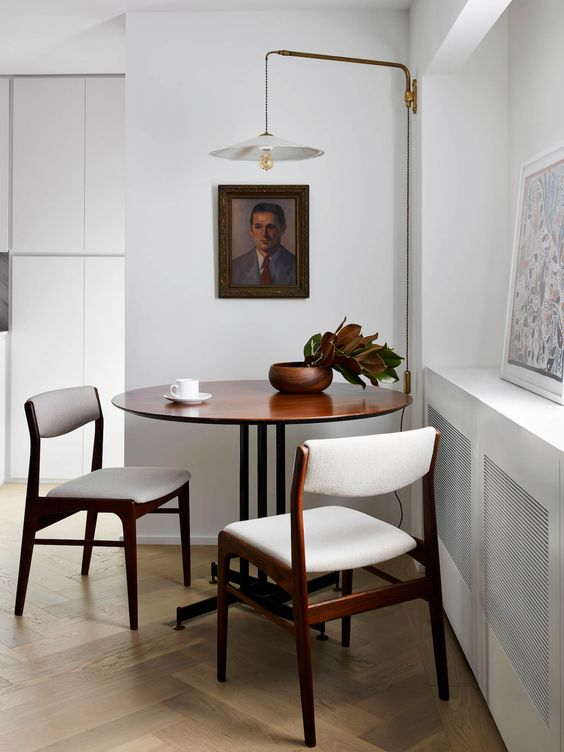 dining room, wood herringbone floor, white wall, dark round wooden table, dark wooden chairs with white seating and back, white lamp