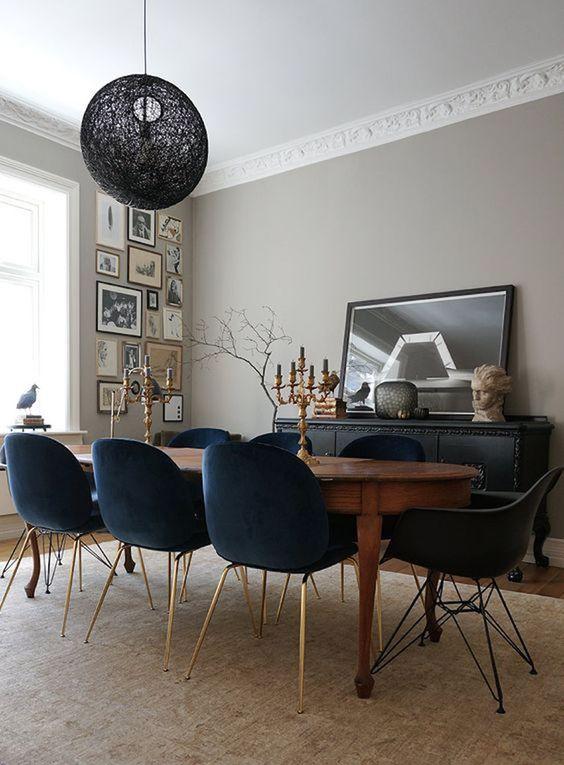 dining room, wooden floor, brown rug, black velvet chairs, wooden long curvy table, black pendant, beige wall, black cabinet