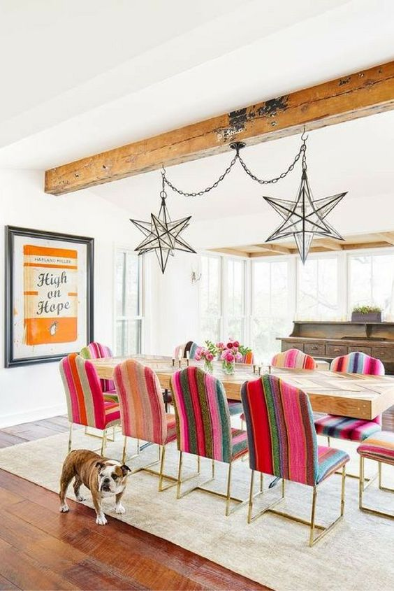 dining room, wooden floor, brown rug, long wooden table with pattern, colorful chairs with golden legs, wooden beams on ceiling, white ceiling, white wall, star pendants