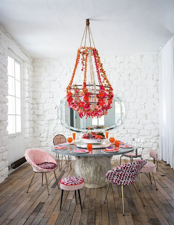 dining room, wooden floor, colorful modern chairs, wooden round floor, white open brick wall, white ceiling, colorful flowery chandelier
