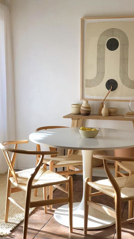 dining room, wooden floor, white tulip table, wooden chairs with woven seating, wooden shelves, rug mat