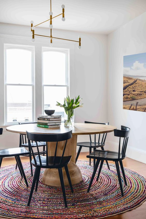 dining room, wooden floor, wooden round table, black wooden chairs, white table
