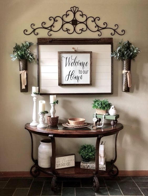 entrance with half round wooden table with metal support, wall decoration, vases,