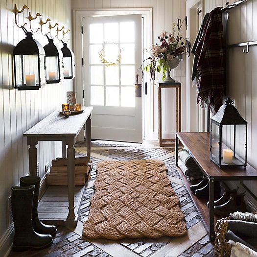 entrance with wooden bench, coat racks, wooden table, candle cage, larga mat