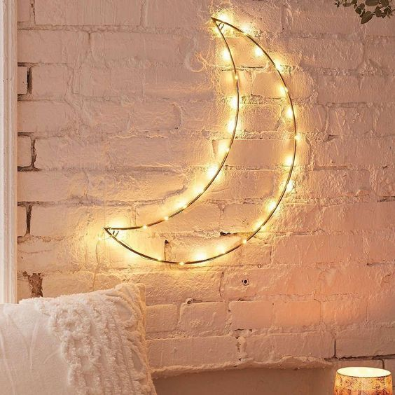 fairy lights following the shape of a quarter of a moon on white open brick wall