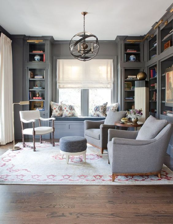 family room with grey wooden wall, built in shelves, gey reading nook on the windowsill, light grey chairs, white chairs, grey ottoman, rug, chandelier