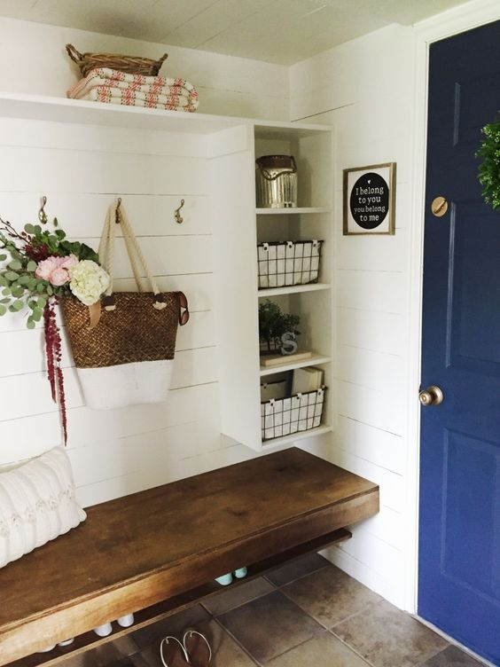floating bench with shoe racks under in entrance with white floating shelves with baskets inside