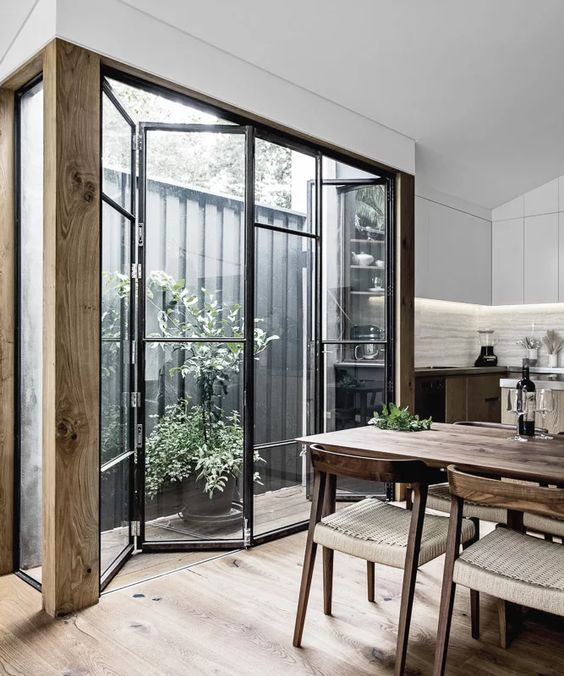 folding glass wall with black metal frame in a kitchen to the oudoor