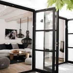 Glass Door With Black Wooden Frame From Living Room To The Backyard