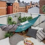 Green Hammock In The Balcony With White Aluminium Fence, Wooden Floor, Rugs, Pillows