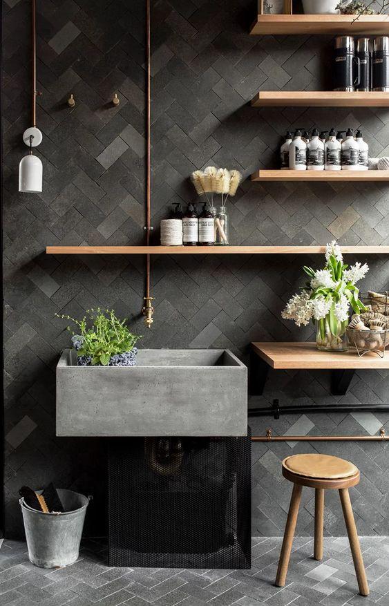 grey bathroom vanity with grey herringbone pattern on floor and wall, wooden floating shelves, wooden stool, white sconces