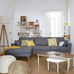 Grey Corner Sofa With Wide Side Without Arm Rest In A Livign Room With Wooden Floor, Rattan Ottoman, Wooden Coffee Table