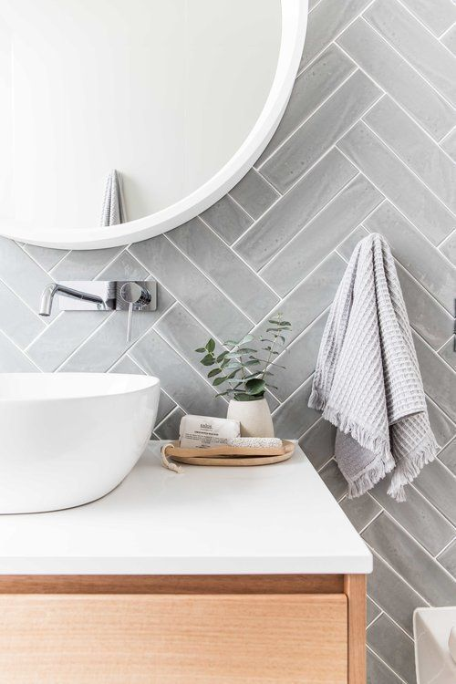 grey herringbone patterned tiles on the wall, white vanity top with wooden cabinet, white sink, silver faucet, white framed mirror