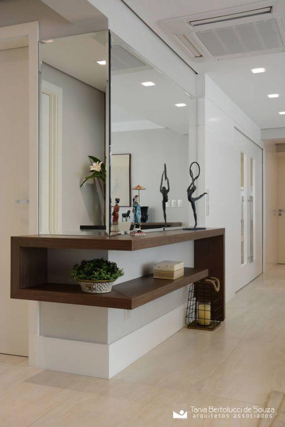 hallway with corner shelves, mirror, white walls, beige floor