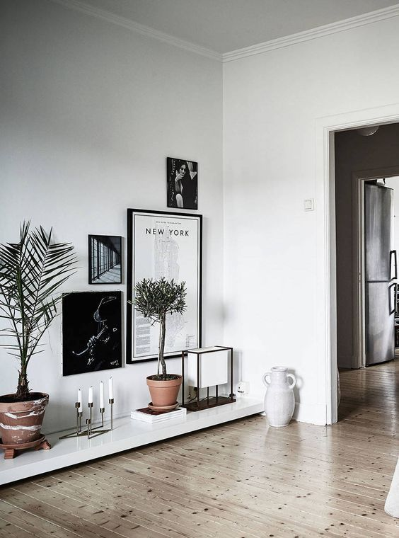 hallway with low floor shelves, plants on the pat, low hanging picture, candles, lamp