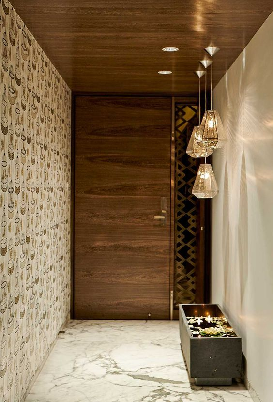 hallway with marble floor, white wall, wallpapered wall, little rectangular pond, glass lamps