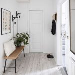 Hallway With White Wooden Floor, White Wall, Wooden Bench, White Pillow, Lamp, Mirror On The Other Side, Hook For Coats