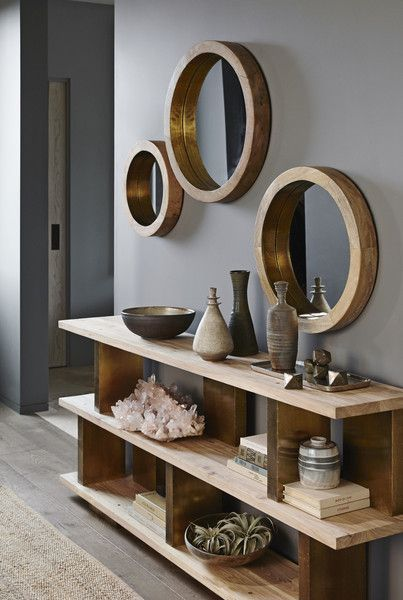 hallway with wooden floor, grey wall, shelves with decorations, round wooden framed mirrors