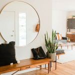Hallway With Wooden Floor, Large Round Mirror, Wooden Bench, Plants, Pillows