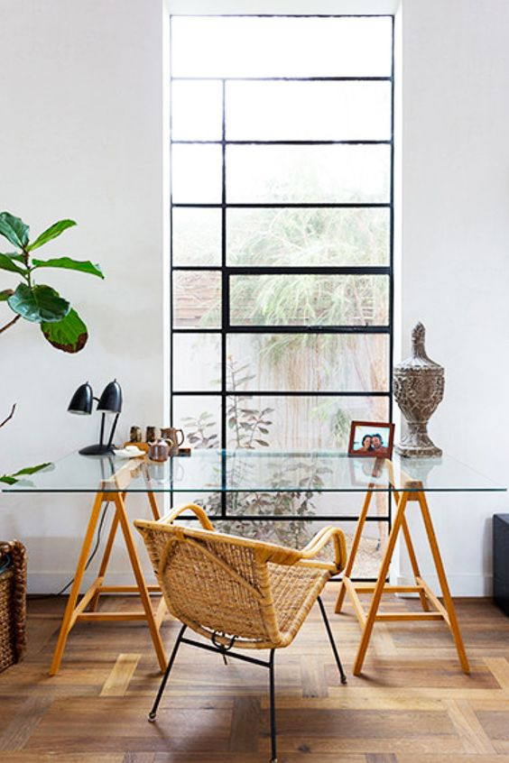 home office with rattan chair, wooden table with glass top, wooden floor, white wall, in front of window