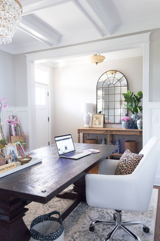 home office with white rug, white chair, dark wooden table, white walls in a room without door