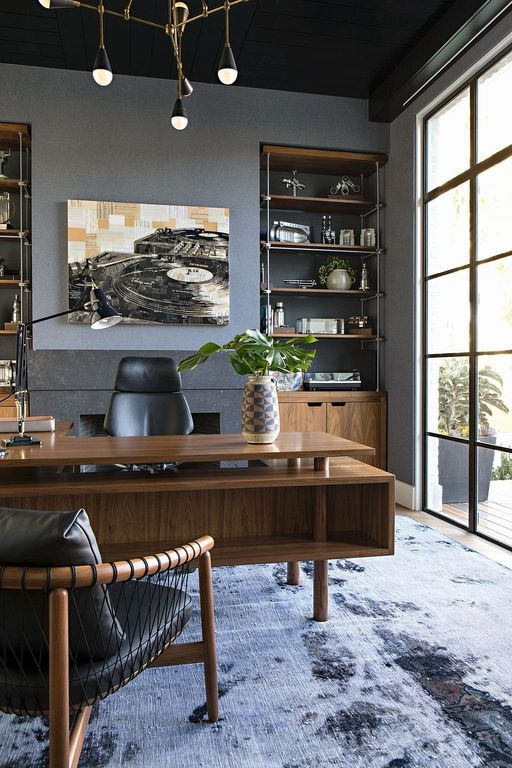 home office with wooden floor, large rug, wooden table, wooden chairs with leather cushion, wooden shelves