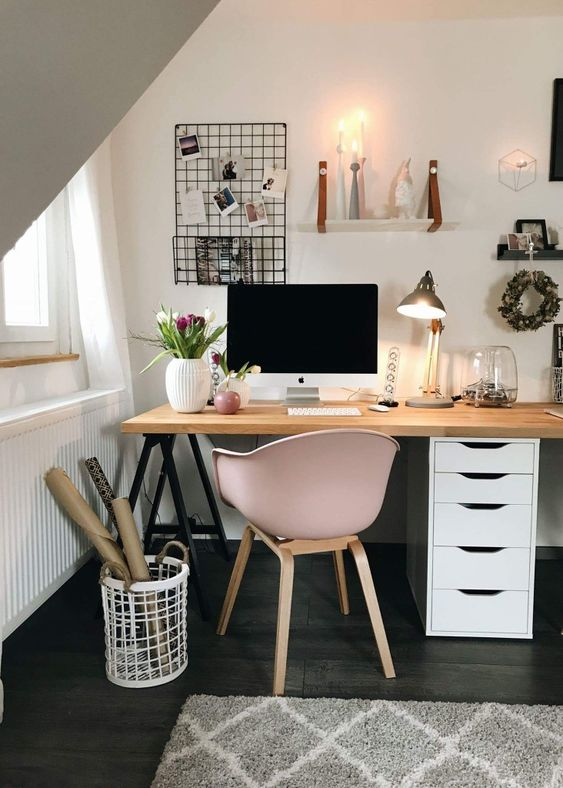 home office with wooden table, rug, brown wooden table with white wooden cabinet, pink chair, white floating shelf