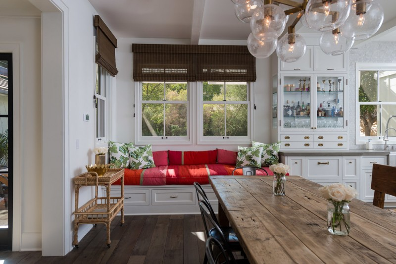 indoor seating cushions colorful cushions wooden floor wooden dining table brass chandelier rattan side table black chairs glass windows roman shade