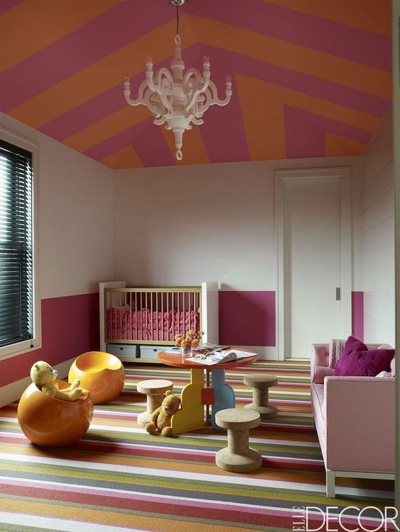 kids bedroom with stripes ruf flooring, pink sofa, round table, stools, chairs, cribs, white and pink wall, pink orange stripes pattern ceiling