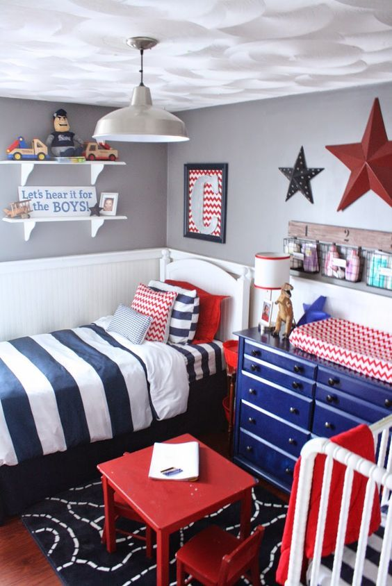 kids bedroom with white and grey wall, striped linene, a bed, a baby crib, blue cabinet, shelves, wall decorations