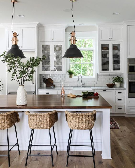 kitcen with wooden floor, white wooden island with dark brown wooden top, rattan stool, white wooden cabinet on top and below the kitchen top