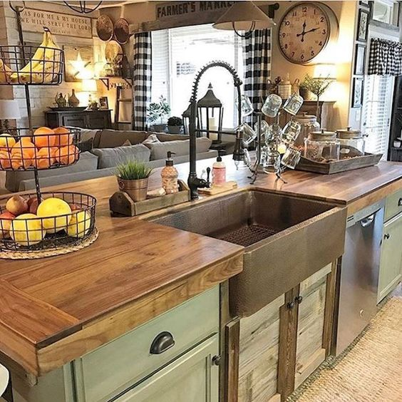 kitchen with ashen look of green wooden cabinet island, with brown wooden top, copper sink, rug,