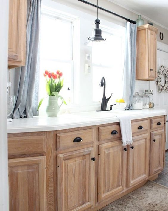 kitchen with brown floor tiles, light brown wooden cabinet with black handles, white counter top black faucet, light brown floating cabinet, white wall, black pendant