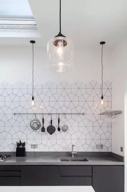 kitchen with dark grey cabinet, dark grey marble counter top, white wall, white geometric tiles, rail for kitchenware