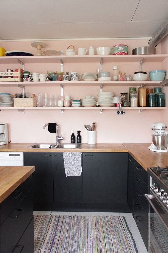 kitchen with grey floor, rug, black cabinet, wooden coutnertop, pink painted wall, pink painted wooden open shelves, black island with wooden top