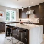 Kitchen With Light Wood Floor, Dark Wood Cabinet And Cupboards, White Marble Backsplash, Counter Top And Island Top, White Wall, Glass Pendant