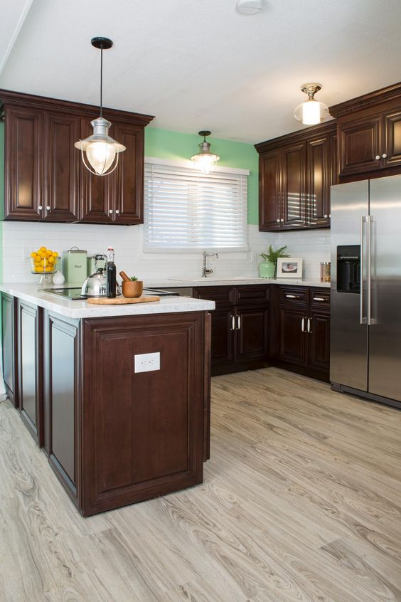 kitchen with light wood floor, dark wood cabinet and floating cabinet with white top, silve fridge, white backsplash, green wall