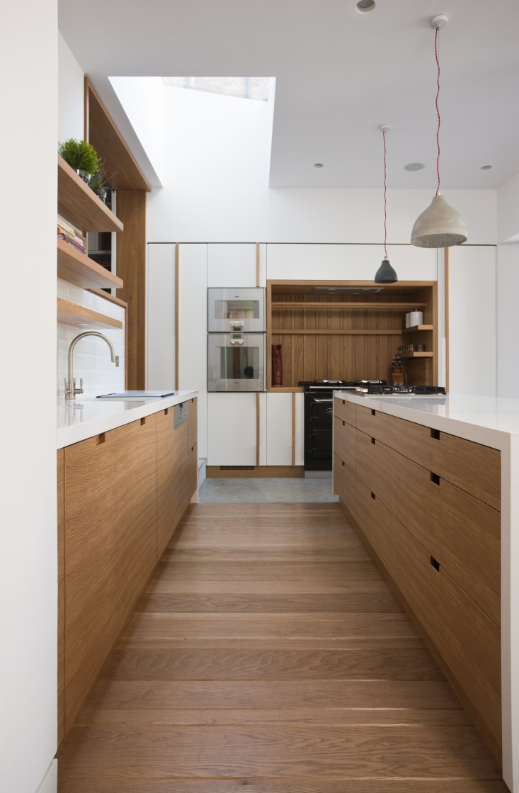 kitchen with light wood floor, light wood cabinet and drawers, floating open shelves, white counter top, white pendant, white wall
