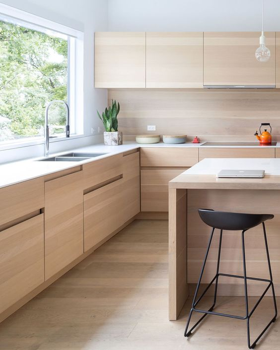 kitchen with light wood floor, light wood in cabinet, backsplash, floating cabinet, islands, white cabinet and island top, white wall