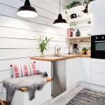Kitchen With Light Wood Flooring, Rug, White Cabinet, Wooden Counter Top, White Shelves, White Wooden Planks Wall, White Storage Box With Wooden Lid